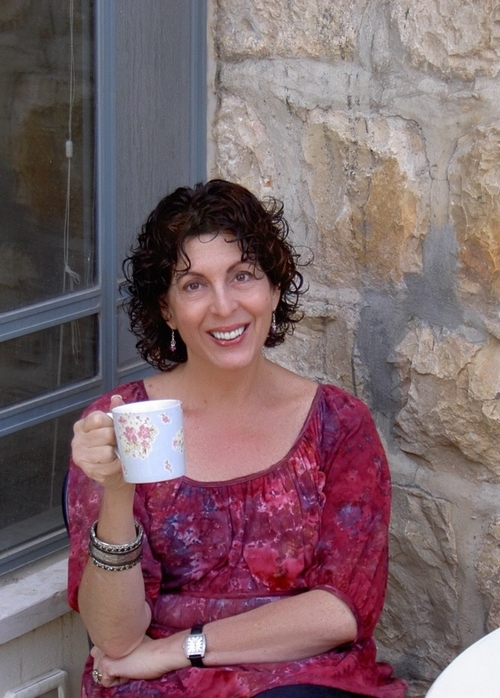 Photo of Sally Abrams smiling and a coffee cup in hand