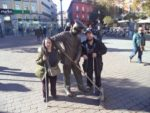 Tony, Tatiana with statue of a street sweeper, in Plaza de Jacinto Benavente.