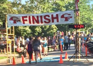 Photo of Kelsi crossing the finish line at the Sturgis 5k.