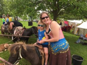 Image of Kelsi and her son on a pony ride at the fair.