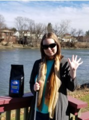 Erin waving Hi near a river and with a package of White Cane Coffee.